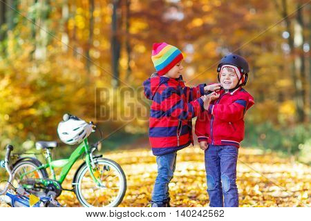 Two little kids boys, best friends in autumn park. Older brother helping younger child to put his bike helmet. Active siblings with bicycles. Happy family