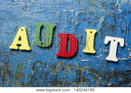 AUDIT word written on colorful wooden letter at abstract blue grunge background.