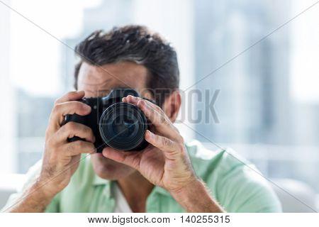 Close-up of man using camera at home