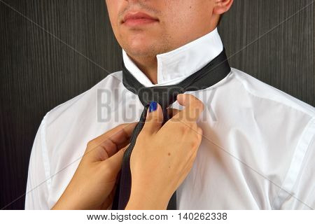 Woman's Hands Adjusting Black Tie And The Neck Of The Shirt. Wife Helping His Husband To Get Dressed