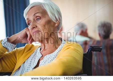Senior woman in wheelchair look worried with hand holding her head