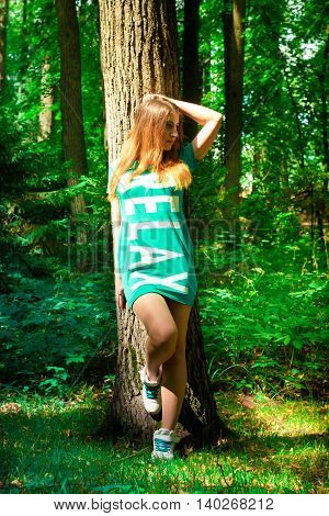The girl and the big tree in the forest. Summer