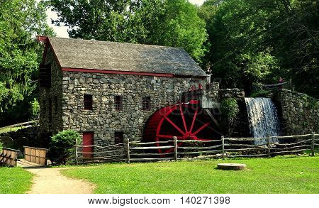 Sudbury Massachusetts - July 12 2013: Old Stone Grist Mill with water wheel and cascade still grinds flour for nearby Longfellow's Wayside Inn