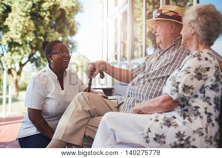 Portrait of senior couple relaxing on a bench outside their retirement home. Caucasian elderly man and woman sitting with female nurse at old age home.