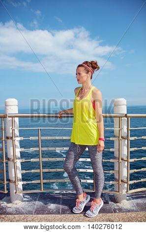 Young Woman In Fitness Outfit Looking Aside At Embankment