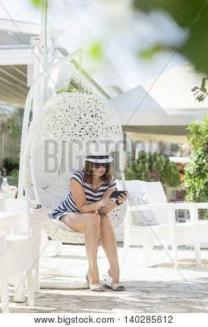 Young woman sitting in a woven rattan hanging chair with cushions enjoying the morning sun in an outdoor cafe by the sea surfing the web on her smart phone