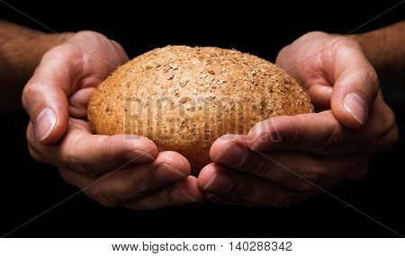 Human hands with bread closeup isolated on black background