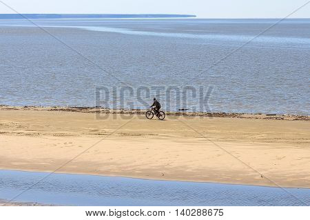 The river Ob Novosibirsk oblast Siberia Russia. A cyclist rides along the shore of the Ob reservoir