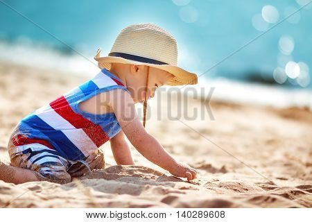 one year old boy playing at the beach in straw hat. Child on family vacations at sea