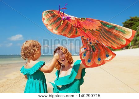 Happy family has fun on sunny sand beach - mother and baby girl walk together along ocean surf and launch old traditional asian kite. Active parent and people activity on summer vacation with children