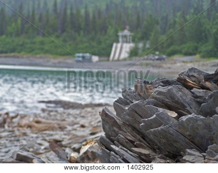 rocky lake shore and trees in Alaska poster