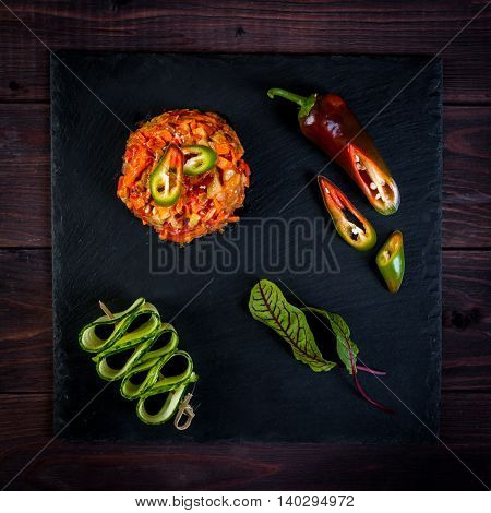 Asian-style stir-fry cooking vegetable saute on slate, wooden background, eggplants, chili pepper, cucumber