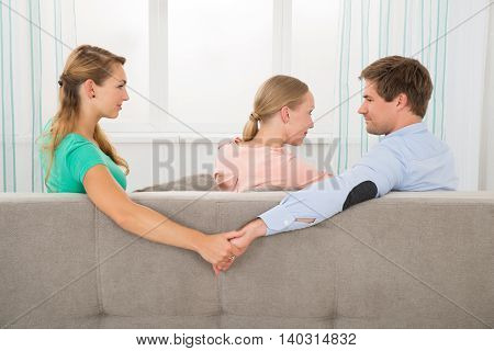Love triangle. Young Man Sitting On Sofa Holding Hands Of His Female Friend While Looking At Girlfriend
