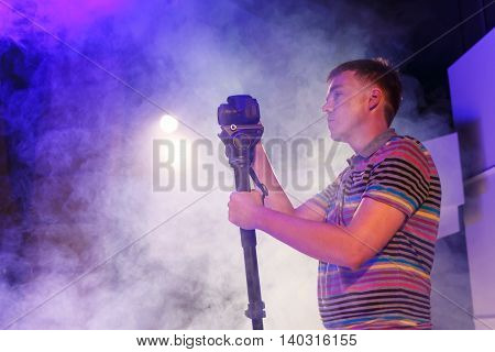 Young operator with a dslr camera shoots video in club