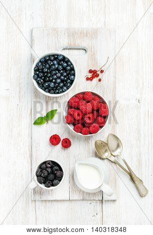 Rasberries, blackberries and bilberries in bowls served with fresh mint, red currant and milk on white painted wooden background, top view, vertical composition