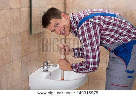 Smiling Young Male Plumber Using Plunger In Clogged Sink In Bathroom