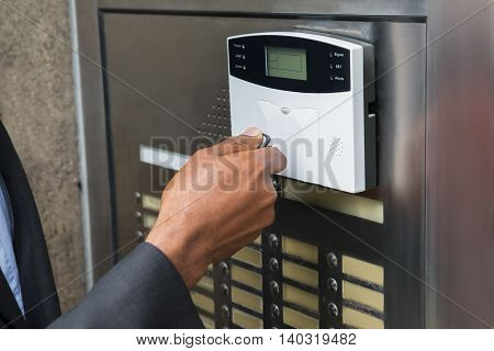 Close-up Of Businessperson's Hand Using Remote Control For Operating Door Security System