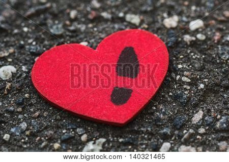 Lonely women's heart with a man's footprint lying on asphalt. Concept of breakup long relations