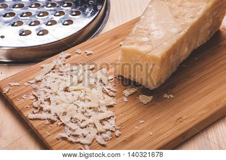 Italian Cheese Parmesan With Grater On Wooden Table