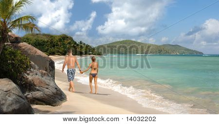 Young romantic couple walking along a tropical beach
