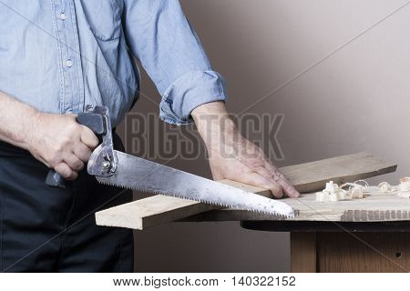 Carpenter working with plane on wooden background at Building Site. Joiner workplace. poster