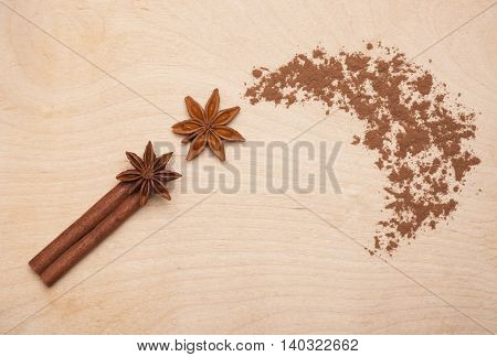 Magic wand made of cinnamon stick, star anise and cocoa powder on wooden background. Magic aromatic spices for healthy and flavored food.