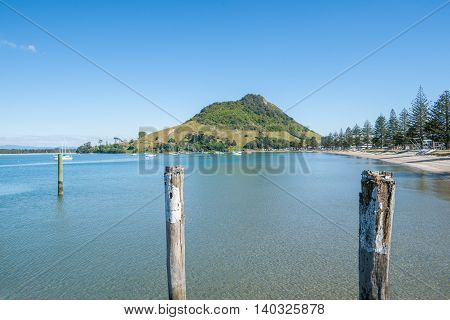 Mount Maunganui along beach of Pilot Bay with three old jetty piles