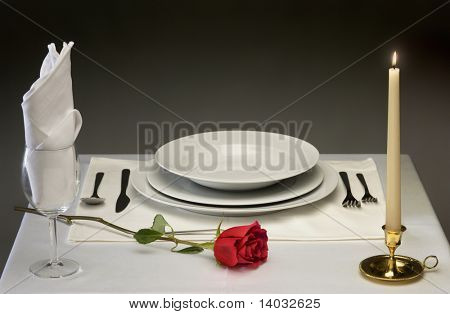 Elegant table setting with rose and candlelight