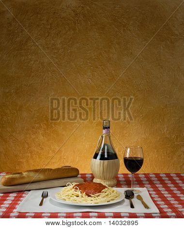 Spaghetti dinner with a baguette and Chianti on a red checkered table cloth with ample background for copy space