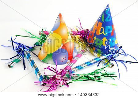 shiny party hats and party blower on white background