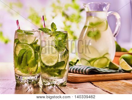 Country drink. On wooden boards glass jug and two glasses with transparent drink and lime . Drink number two hundred eighty eight with ice cubes . Country life. Light background.