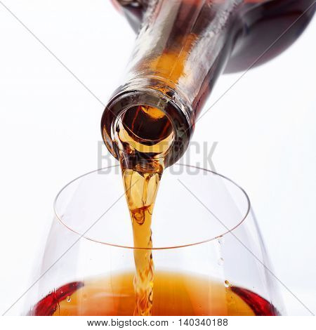Luxury cognac or brandy pour into glass for brandy closeup on white background