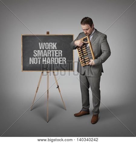 Work smarter not harder text on blackboard with businessman and abacus