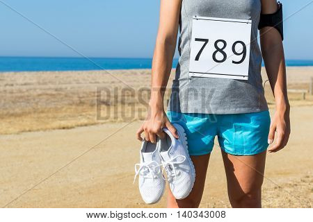 Close up of female athlete with dorsal start number holding running shoes. Body part of girl outdoors at beachfront.