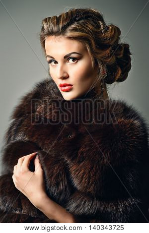 Close-up portrait of a beautiful woman in luxurious fur coat. Luxury, rich lifestyle. Jewellery. Fashion shot.