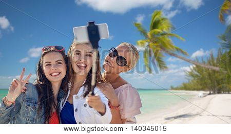 summer vacation, holidays, travel, technology and people concept- group of smiling young women taking picture with smartphone on selfie stick over tropical beach background