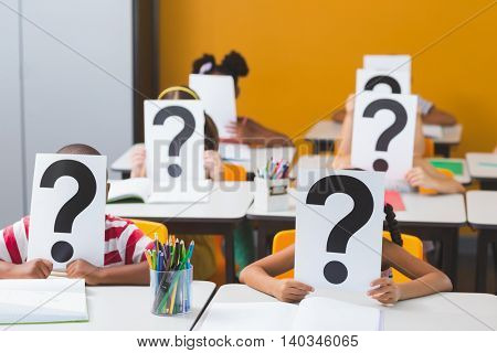 School kids covering their face with question mark sign in classroom at school