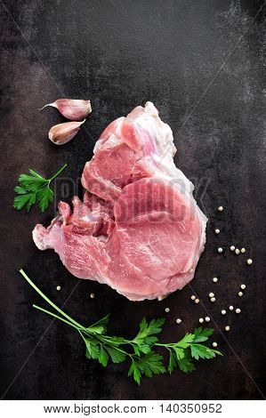 raw meat on dark metal background top view