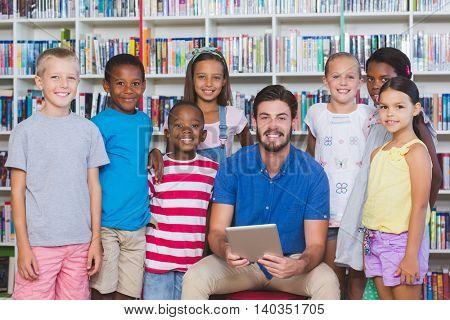 Teacher teaching kids on digital tablet in library at elementary school