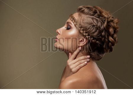 Beauty woman with beautiful make-up color . Brown hair braids of hair clean shiny skin beauty face . Portrait shot in studio on a green background .