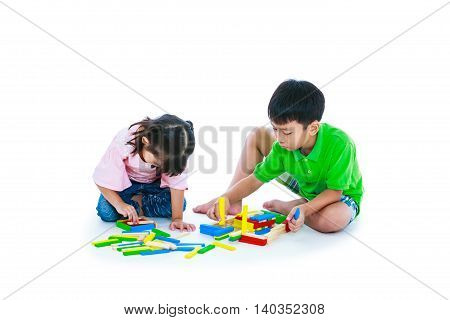 Happy asian children. Boy and girl playing toy wood blocks isolated on white background. Educational toys for elementary and kindergarten child. Strengthen the imagination of child. Studio shot.
