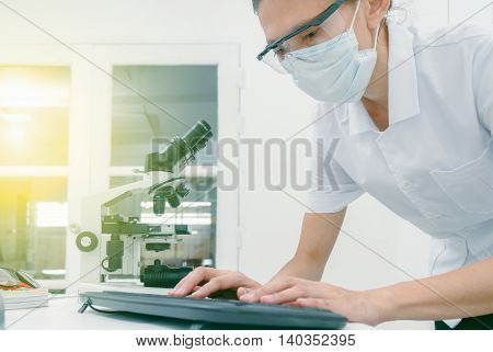 Female Medical Or Scientific Researcher Or Woman Doctor Using A Computer In A Laboratory With Micros