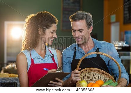Staff members maintain records on clipboard in supermarket