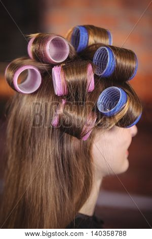Woman with hair roller on hair at a salon