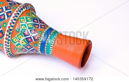 Still life showing an angled view of an Egyptian decorated orange pottery vase on white background