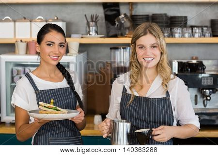 Portrait of two waitresses holding plate of meal and coffee jug in cafe