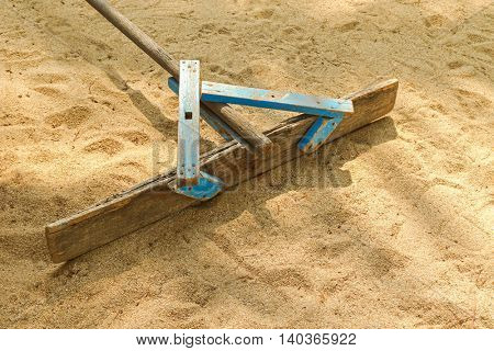 Handmade wooden stick to flatten, level and smooth surface of sand on the beach