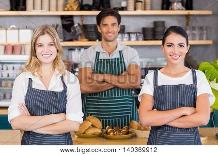 Smiling waiter and two waitresses standing with arms crossed in cafe