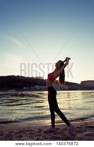 Portrait Of Young Healthy Sporty Woman Stretching On Beach
