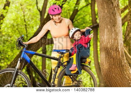 Little toddler girl in bike helmet and seat with her mother during bike ride in spring wood